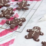 gingerbread cookies with red and green striped towel on white backdrop